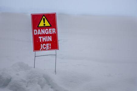 thin ice warning near a frozen lake 免版税图像