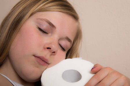 Girl hugs a single roll of toilet paper during the pandemic Standard-Bild