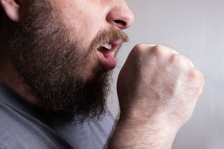 man not curbing the spread of disease by coughing into his hand