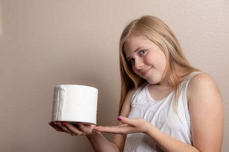 Younggirl holding up toilet paper that she has
