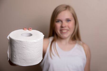 young girl holding out a roll of toilet paper