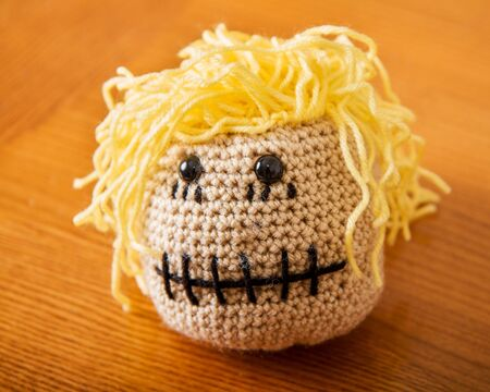 Ball head made from yarn with a mouth sewed shut