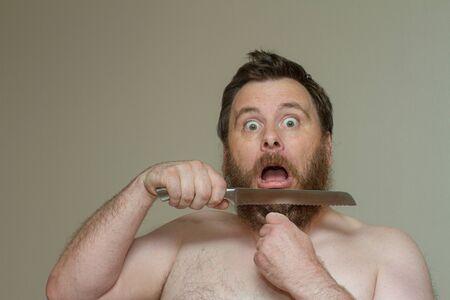 Man cutting his hair with a sharp knife Standard-Bild