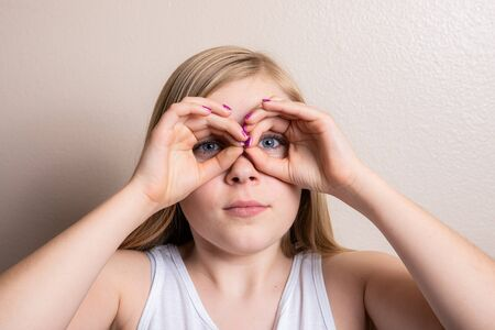 Young girl pretending to look through binoculars
