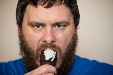 Man angrily protecting his ice cream he is eating