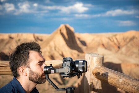 young filmmaker filming natural landscape in canyon with a large river and marshes