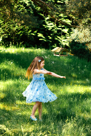 swirling: Beautiful little swirling girl in a blue dress with a blue bag in summer garden