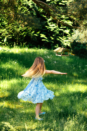 whirling: Beautiful little swirling girl in a blue dress with a blue bag in summer garden