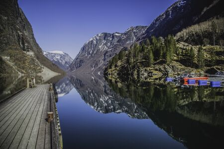 Fjord in Norway mountains and small bridge reflection in water all in color