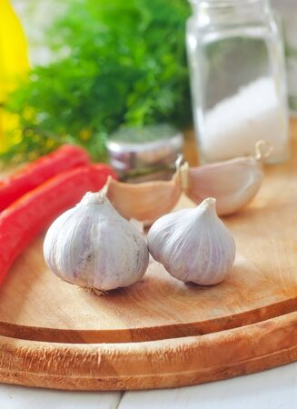Fresh garlic and aroma spice on the wooden board photo
