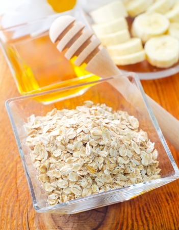 Raw oat flaks in the glass bowl photo