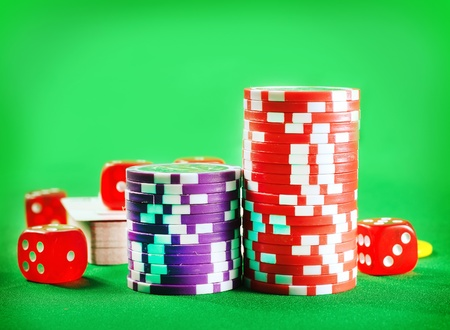 Chips for poker and cubes on the green background photo