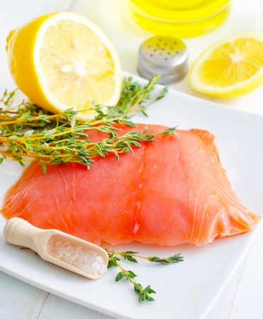 Raw salmon on the white plate with thyme and salt photo
