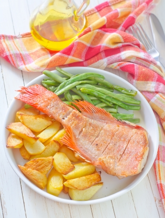 baked fish with potato and green beans photo