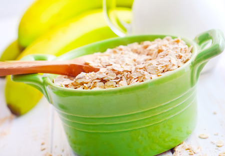 Oat flakes in the green bowl with banana and milk photo