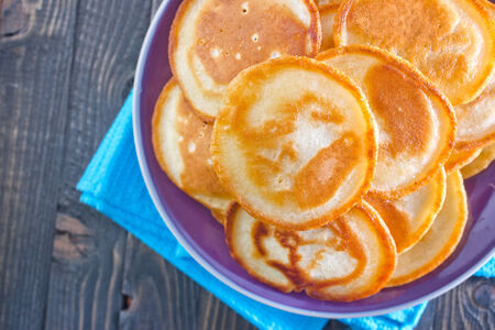 pancakes on the  plate and on a table photo