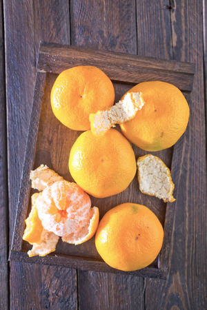orange peel clove: tangerines in wooden box and on a table