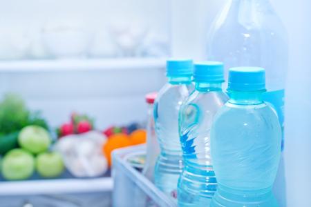 冷蔵庫のフル ボトルに水、食品の