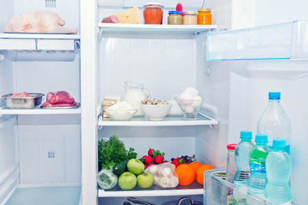 refrigerator with food: Refrigerator full of food, water in bottles Stock Photo