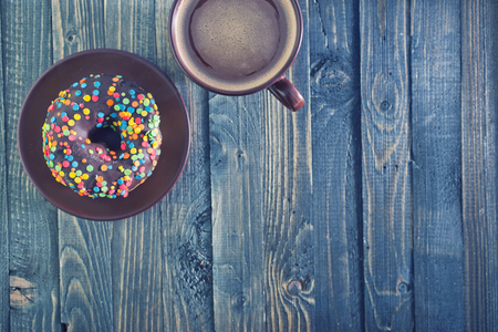 chocolate donuts and coffee in cup on a table photo