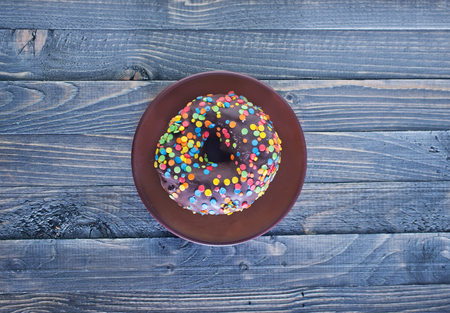 chocolate donut on plate and on a table photo
