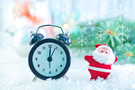 clock and christmas decoration on the snow photo