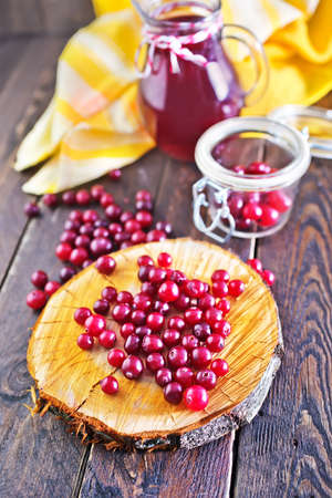 cranberry on the wooden board and on a table photo