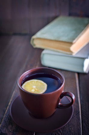 stimulated: tea with lemon in cup and old books