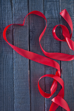 red heart ribbon on the wooden background photo