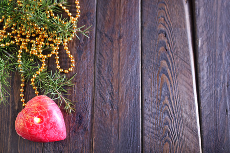 One red candle on the wooden table photo
