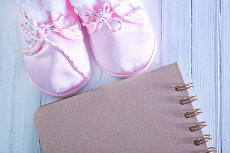 baby shoes and notepad for note on a table photo