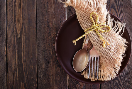 grunge silverware: spoon, fork and knife on plate and on a table Stock Photo