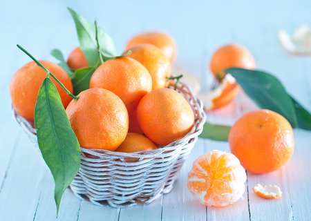 fresh tangerines in basket and on a table photo