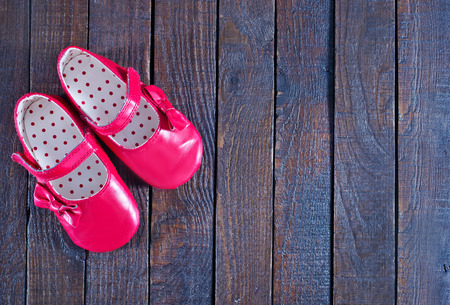 patent leather: red baby shoes on the wooden background