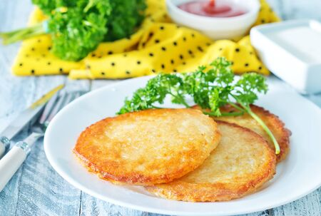 potato pancakes on plate and on a table photo
