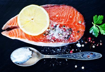 rosmarin: raw salmon steak with spice on the black board Stock Photo