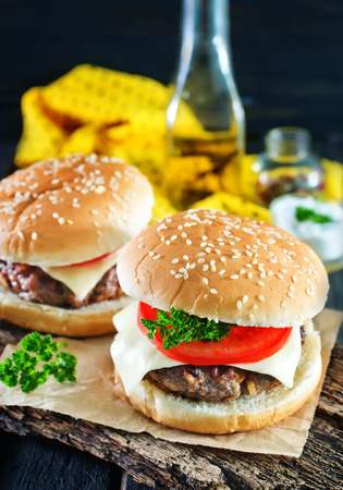 cheeseburgers: cheeseburgers on board and on a atble Stock Photo