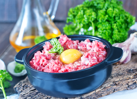 minced meat and raw egg in bowl and on a table photo