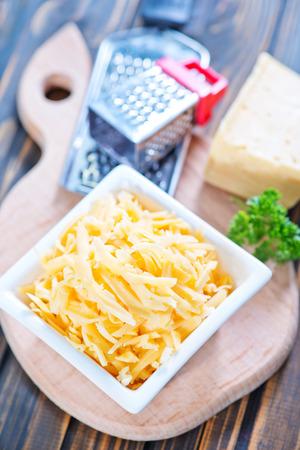 queso rayado: queso rallado en un taz�n y sobre una mesa Foto de archivo
