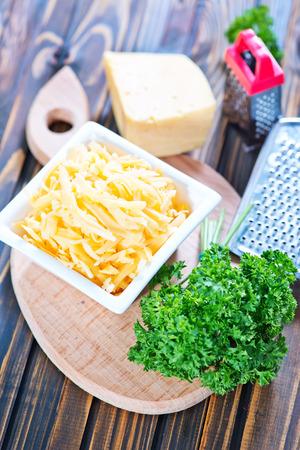 grated cheese: queso rallado en un taz�n y sobre una mesa Foto de archivo