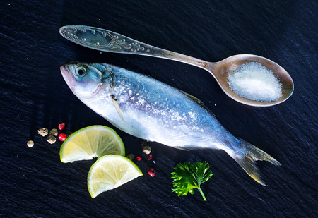raw fish and salt on the black board photo