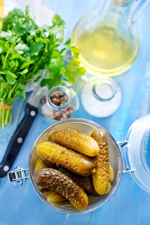 marinated gherkins: cucumbers in bowl and on a table
