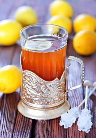 fresh tea with lemon in cup and on a table photo