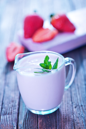 lactic: strawberry yogurt in glass jug and on a table