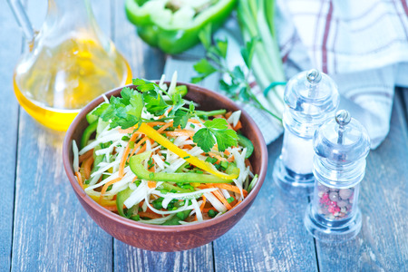fresh salad in bowl and on a table photo