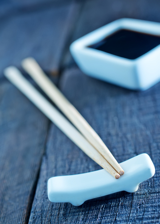 hoisin: soy sauce and bamboo sticks on a table