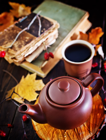 homestyle: fresh tea in teapot on wooden board and on a table