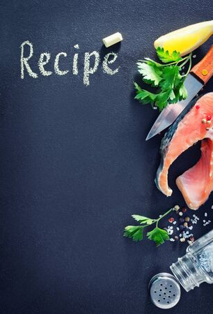 rosmarin: board for recipe and raw fish on a table