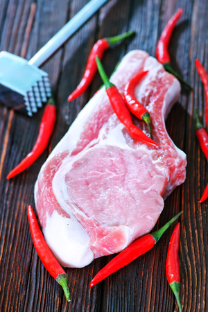 meat lover: raw meat with chilli peppers on the wooden table
