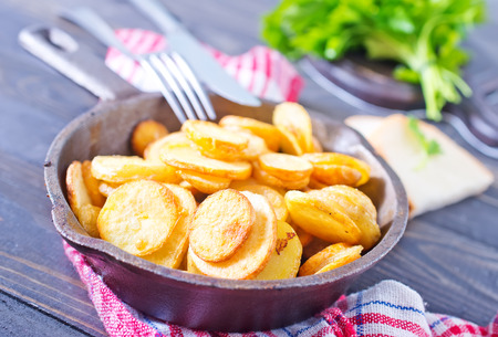 potato fries: fried potato in pan and on a table Stock Photo